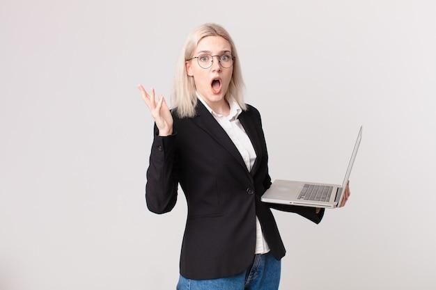 Blonde mooie vrouw die zich extreem geschokt en verrast voelt en een laptop vasthoudt