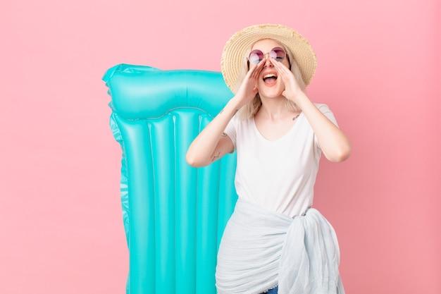 Blonde mooie vrouw die zich gelukkig voelt, een grote schreeuw geeft met de handen naast de mond. zomer concept