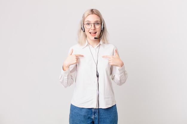 Blonde mooie vrouw die zich gelukkig voelt en naar zichzelf wijst met een opgewonden telemarketingconcept