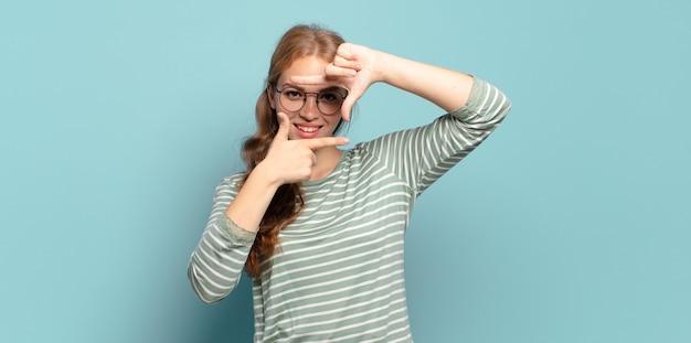Blonde, mooie vrouw die zich gelukkig, vriendelijk en positief voelt, lacht en een portret of fotolijst met handen maakt