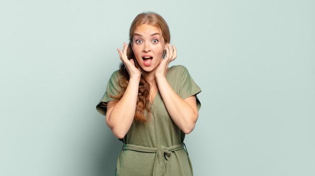 Blonde mooie vrouw die zich geschokt en opgewonden voelt, lacht, verbaasd en blij vanwege een onverwachte verrassing