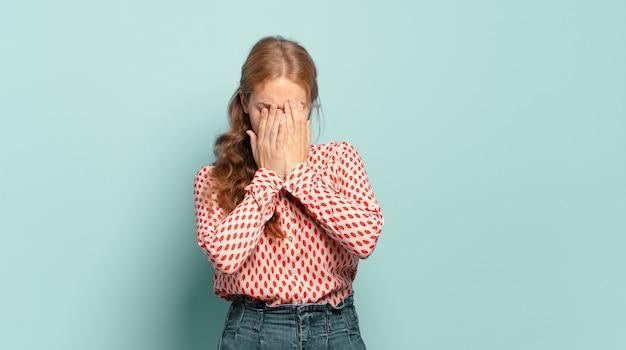 Blonde, mooie vrouw die zich verdrietig, gefrustreerd, nerveus en depressief voelt, haar gezicht met beide handen bedekt, huilt