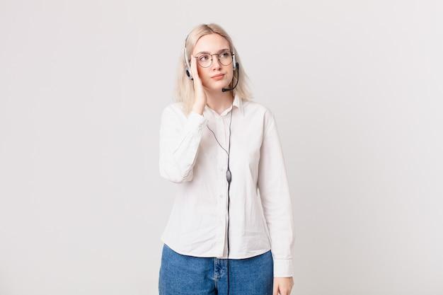 Blonde mooie vrouw die zich verveeld, gefrustreerd en slaperig voelt na een vermoeiend telemarketingconcept