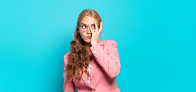 Blonde mooie vrouw die zich verveeld, gefrustreerd en slaperig voelt na een vermoeiende, saaie en vervelende taak, haar gezicht met de hand vasthoudend