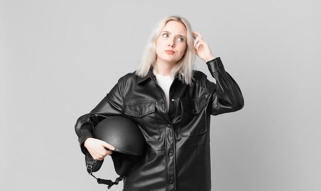 Blonde mooie vrouw die zich verward en verward voelt, hoofd krabben. motorrijder concept