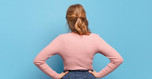 Blonde mooie vrouw die zich verward of vol voelt of twijfels en vragen, zich afvraagt, met de handen op de heupen, zicht naar achteren