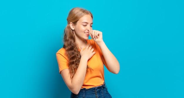 Blonde mooie vrouw die zich ziek voelt met een zere keel en griepsymptomen, hoesten met bedekte mond