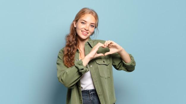 Blonde mooie vrouw glimlacht en voelt zich gelukkig, schattig, romantisch en verliefd, hartvorm makend met beide handen