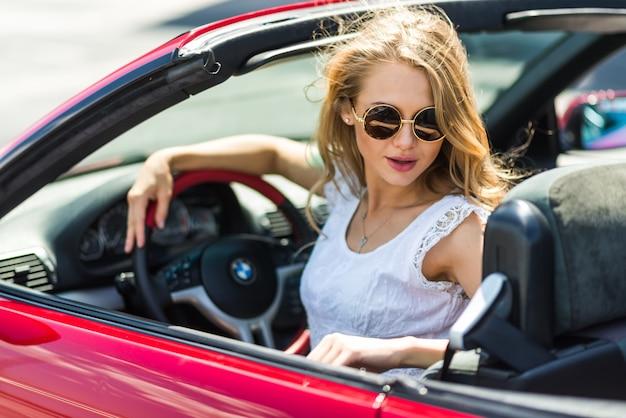 Blonde mooie vrouw in zonnebril zitten in rode auto bij de zee. zeezicht. vakantieconcept. happyness. vrijheid. wegroute op mooie zonnige zomerdag