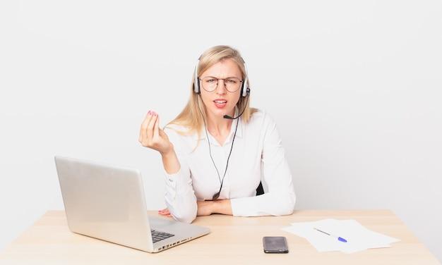 Blonde mooie vrouw jonge blonde vrouw die capice of geldgebaar maakt, je vertelt te betalen en met een laptop werkt