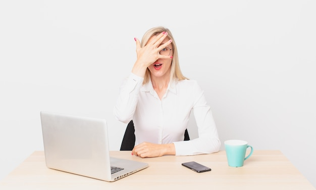 Blonde mooie vrouw jonge blonde vrouw die geschokt, bang of doodsbang kijkt, haar gezicht bedekt met de hand en met een laptop werkt