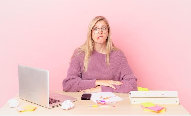 Blonde mooie vrouw jonge blonde vrouw die verbaasd en verward kijkt en met een laptop werkt