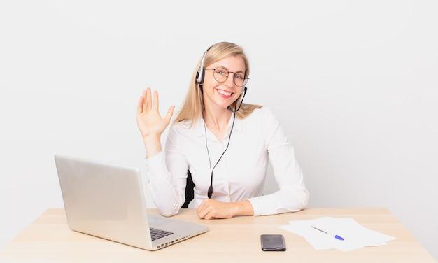Blonde mooie vrouw jonge blonde vrouw die vrolijk lacht, met de hand zwaait, je verwelkomt en begroet en met een laptop werkt