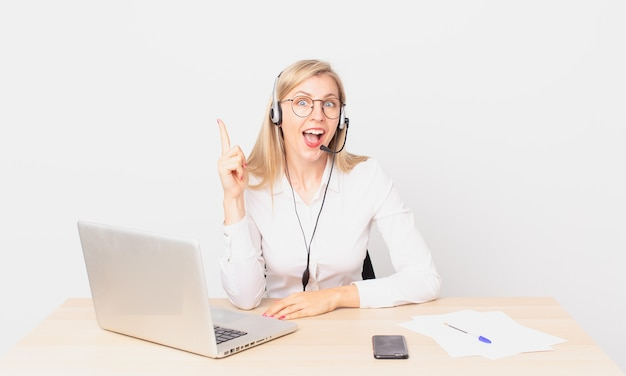 Blonde mooie vrouw jonge blonde vrouw die zich een gelukkig en opgewonden genie voelt na het realiseren van een idee en het werken met een laptop