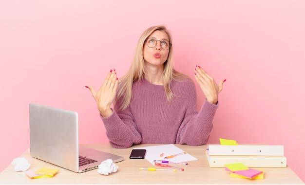 Blonde mooie vrouw jonge blonde vrouw die zich gestrest, angstig, moe en gefrustreerd voelt en met een laptop werkt