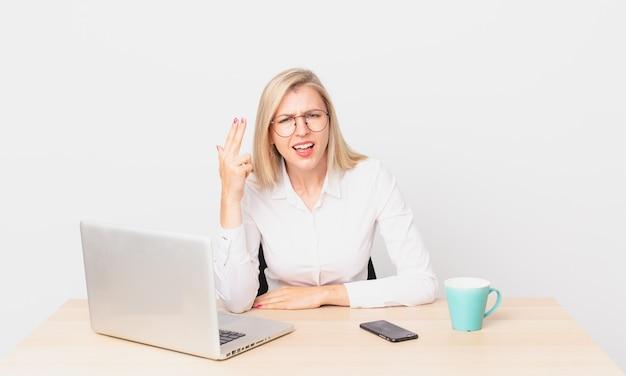 Blonde mooie vrouw jonge blonde vrouw die zich verward en verbaasd voelt, laat zien dat je gek bent en met een laptop werkt