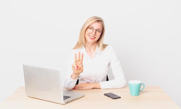 Blonde mooie vrouw jonge blonde vrouw lacht en ziet er vriendelijk uit, toont nummer drie en werkt met een laptop