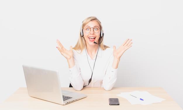 Blonde mooie vrouw jonge blonde vrouw voelt zich gelukkig en verbaasd over iets ongelooflijks en werkt met een laptop Premium Foto