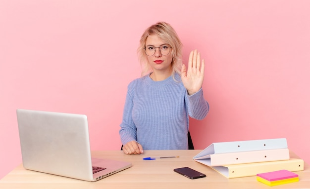 Blonde mooie vrouw jonge mooie vrouw die er serieus uitziet en open palm toont die een stopgebaar maakt. werkruimte bureau concept