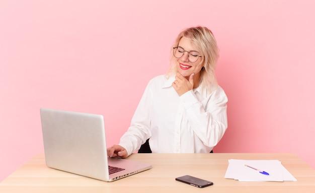 Blonde mooie vrouw jonge mooie vrouw die lacht met een vrolijke, zelfverzekerde uitdrukking met de hand op de kin. werkruimte bureau concept