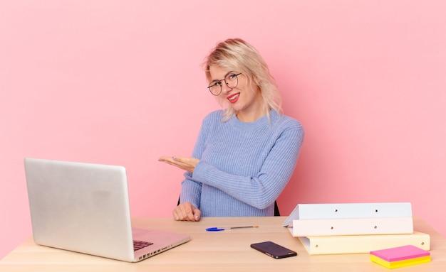 Blonde mooie vrouw jonge mooie vrouw die vrolijk lacht, zich gelukkig voelt en een concept toont. werkruimte bureau concept