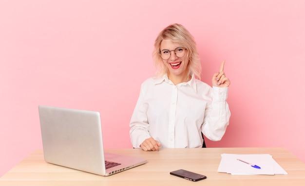 Blonde mooie vrouw jonge mooie vrouw die zich een gelukkig en opgewonden genie voelt na het realiseren van een idee. werkruimte bureau concept