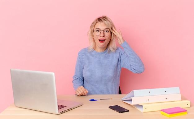 Blonde mooie vrouw jonge mooie vrouw op zoek gelukkig, verbaasd en verrast. werkruimte bureau concept