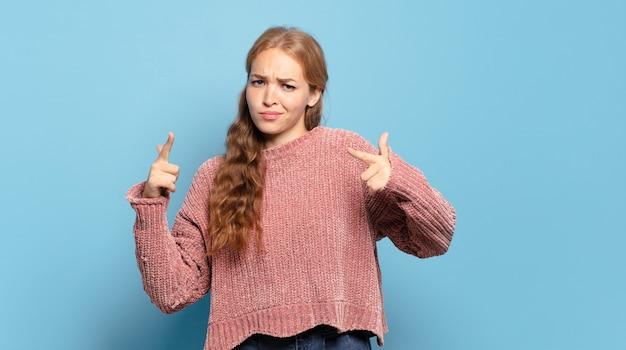 Blonde mooie vrouw met een slechte houding die er trots en agressief uitziet, naar boven wijst of een leuk teken maakt met handen