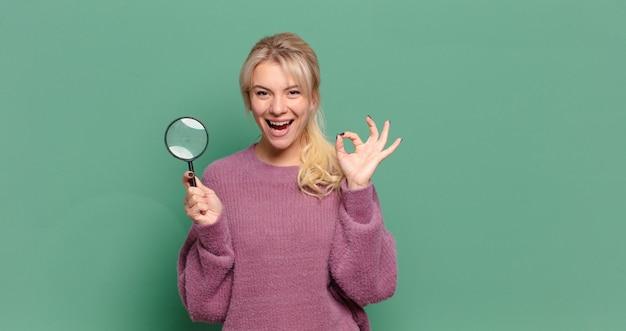 Blonde mooie vrouw met een vergrootglas