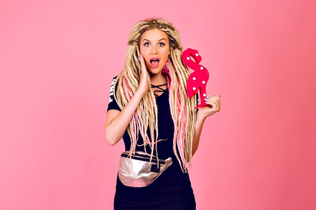 Blonde mooie vrouw met lange blonde dreadlocks met plastic flamingo, stijlvolle sport chique outfit, verrast emoties, pop laatste stijl dragen.