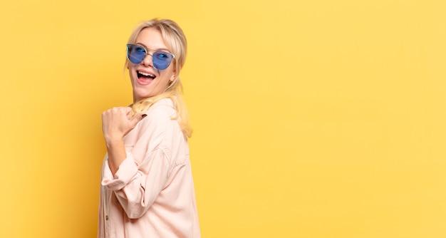 Blonde mooie vrouw met zonnebril die naar achteren wijst