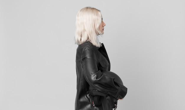 Blonde mooie vrouw op profielweergave denken, verbeelden of dagdromen. motorrijder concept