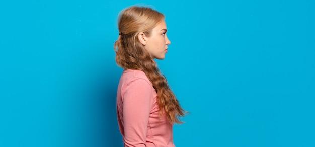Blonde mooie vrouw op profielweergave die ruimte vooruit wil kopiëren, denken, fantaseren of dagdromen