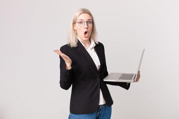 Blonde mooie vrouw verbaasd, geschokt en verbaasd met een ongelooflijke verrassing en met een laptop