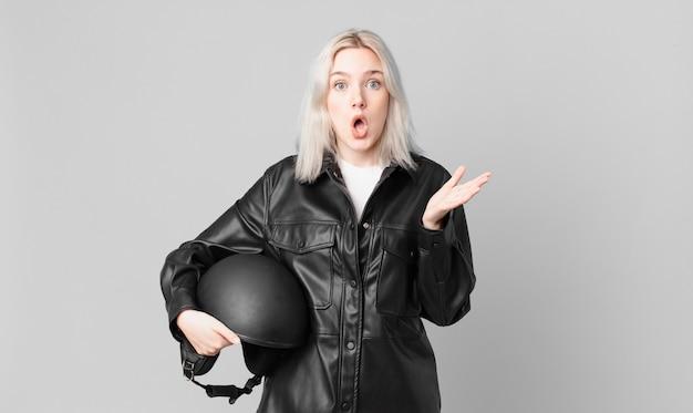 Blonde mooie vrouw verbaasd, geschokt en verbaasd met een ongelooflijke verrassing. motorrijder concept