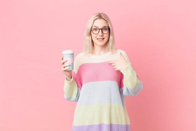 Blonde mooie vrouw voelt zich gelukkig en wijst naar zichzelf met een opgewonden koffie concept