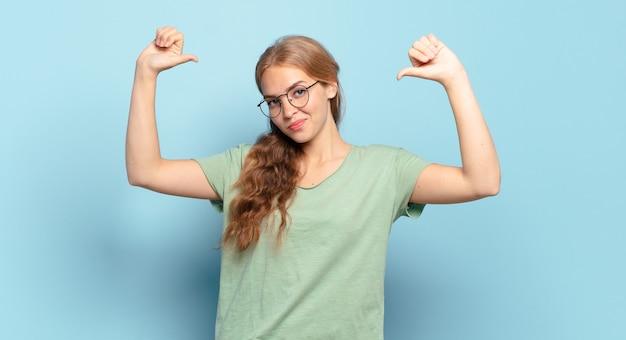 Blonde mooie vrouw voelt zich trots, arrogant en zelfverzekerd, ziet er tevreden en succesvol uit en wijst naar zichzelf