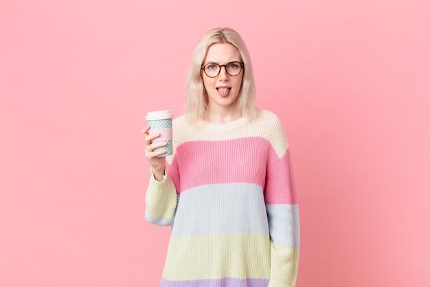 Blonde mooie vrouw walgt en geïrriteerd en tong uit. koffie concept