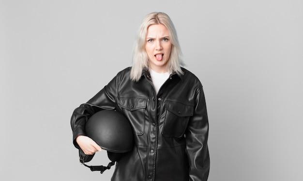 Blonde mooie vrouw walgt en geïrriteerd en tong uit. motorrijder concept