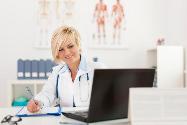 Blonde mooie vrouwelijke arts werkzaam in haar kantoor