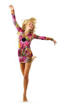 Blonde mooie vrouwenmodellen in roze jurk met oosters patroon springen en dansen over witte muur. schoonheid en mode levensstijl concept