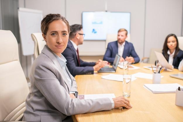 Blonde mooie zakenvrouw zittend aan tafel tegen collega's