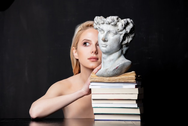 Blonde naast een antieke buste van een man op boeken