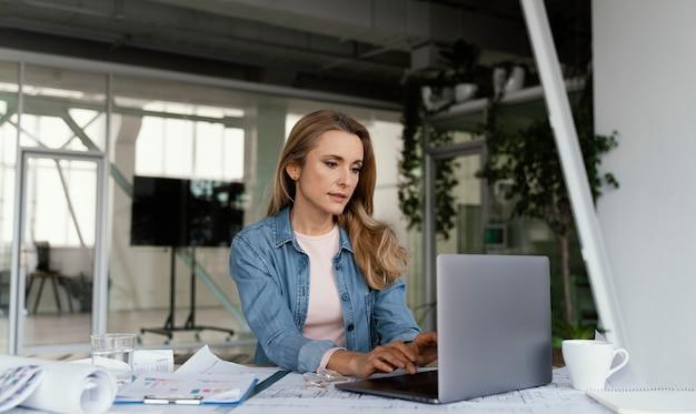 Blonde onderneemster die bij haar laptop werkt