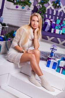 Blonde op witte kerstversiering op het terras naast de geschenken