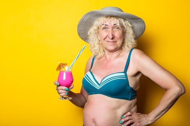Blonde oude vrouw in een zwembroek houdt een cocktail op een gele ondergrond