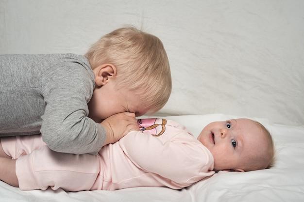 Blonde oudere broer speelt met zijn kleine zusje