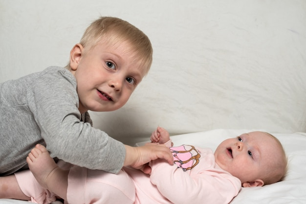 Blonde oudere broer speelt met zijn kleine zusje.