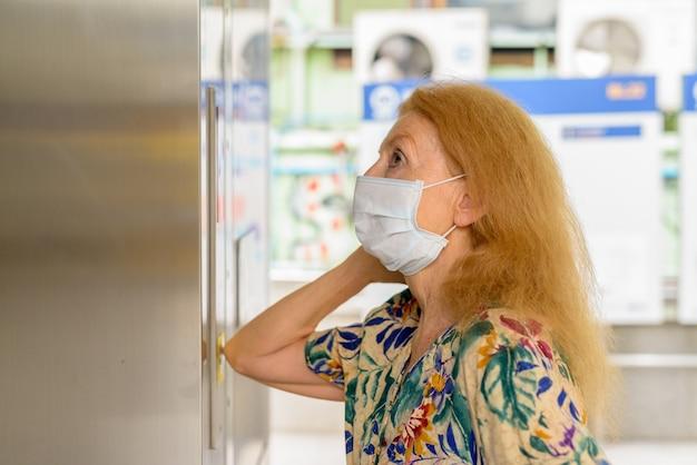 Blonde oudere vrouw die met masker op de liftknop met elleboog drukt om verspreiding van het coronavirus covid-19 te voorkomen