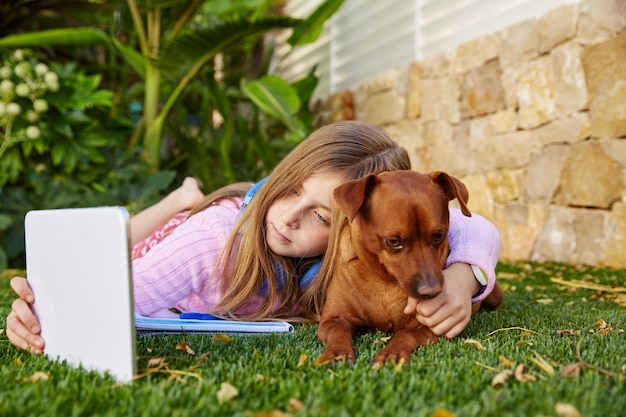 Blonde pc van de de fototablet van de jong geitjemeisje selfie en hond
